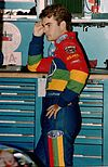 A man his late twenties wearing rainbow colored racing overalls. He has his left hand on his left hip and his right hand leaning against a solid surface.