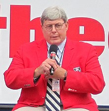 A man with glasses and a red coat speaks into a microphone.