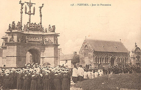 Photograph held by the Musée national des arts et traditions Populaires in Pleyben showing a procession passing by the Pleyben calvary on an unspecified date between 1903 and 1920.