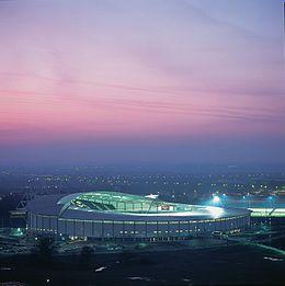 En vy i skymningen som tittar ner på en modern starkt upplyst cirkulär fotbollsstadion