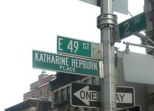 "A street sign that reads ""E 49 St"", with another underneath it that reads ""Katharine Hepburn Place""."