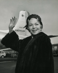 Woman in a fur coat, waving and smiling