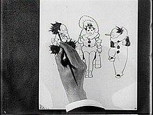 Film fortfarande av en hand som skisserar tre seriefigurer