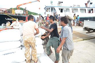 Vanua Balavu - Men loading bags of copra and other crops onto an inter-island vessel at Lomaloma wharf, Vanua Balavu for markets in Suva the capital of Fiji.