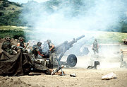 M102 howitzers firing during battle.