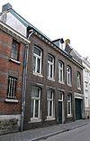 foto van Huis, met in de vernieuwde voorgevel segmentboogvensters in hardsteen, en een koetspoort in hardstenen omlijsting.