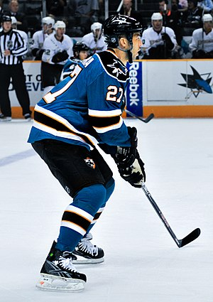 Manny Malhotra -  alt = An ice hockey player, seen from the side, in a ready position. He is slightly crouched while standing on his skates and holds his stick in both hands. He wears a teal jersey with black trim, as well a black helmet.