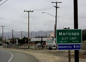 Northern city limit of Maricopa; the fire in the center is a gas flare from an active oil well