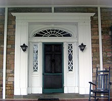 A green door in a white frame with a semi-circular window above with spider-web like rays. On either side of the door are windows with elaborate frameworks, along with two black lanterns, and stone walls. A rocking chair is at right.