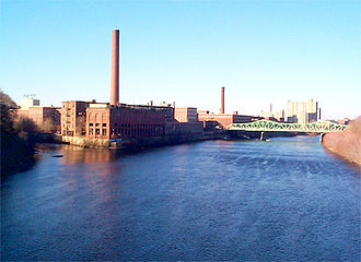 Lowell, Massachusetts - The Massachusetts Mill at the confluence of the Merrimack and Concord Rivers; across the Cox Bridge are the Boott Mills; in the upper left is the historic Lowell Sun building with its iconic sign on top.