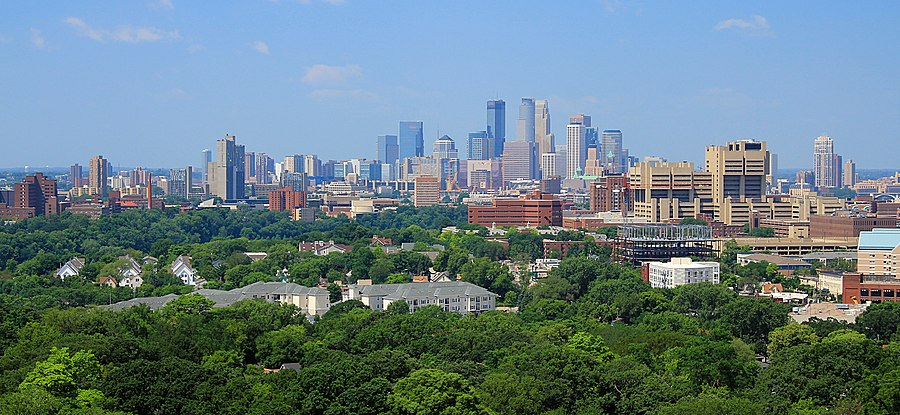 The Minneapolis skyline rises to its highest point at the center of the image, with the three tallest buildings standing out against a clear blue sky. Before the skyline are trees, university buildings, and residential complexes.