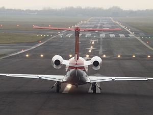 Runway - A Phenom 300 from behind at one end of a runway
