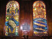 Two tall stained glass windows. The left window shows an aircraft carrier about to launch an aircraft, while the right depicts two cruisers and an aircraft carrier at sea. A memorial plaque sits between the windows.