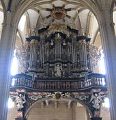 The organ of the Severikirche in Erfurt, Germany, features a highly decorative case with ornate carvings and cherubs.
