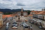 Two-storied white buildings with red roof tiles lining a square. At the end of the square there is a prominent building with a clock tower.