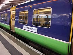 an old unit in purple and green design with a London Overground sticker