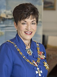 A smiling woman wearing insignia of the governor-general