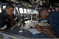 Philippine navy Cmdr. Mario O Argel, left, a safety officer for exercise Balikatan 2013, observes as U.S. Navy Quartermaster 3rd Class Kaion Abrahams records information into a deck log on the bridge of 130409-N-IY633-004.jpg