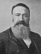 A man with a huge beard and a dark jacket