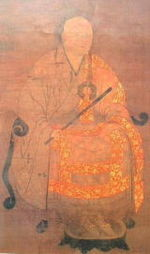 Priest seated on a chair holding a stick-like object in his hand.
