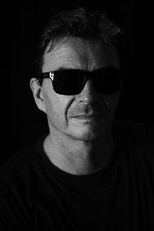Black and white photographic portrait of a man in his fifties with black sunglasses. The man is looking straight in front of him