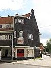 foto van Blok met winkels met brede luifel en daarboven woningen, bouwstijl Amsterdamse School, onderdeel van het centrale achthoekige plein van Tuindorp Nieuwendam