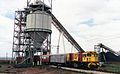 QR loco 1740 hauls a special train through a coal loading facility, Goonyella line ~1991.jpg