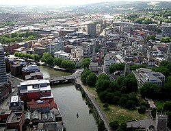 A view from above of office blocks and church spires adjacent to a river which is crossed by a road bridge. In the right foreground a city park and a ruined church. A small boat is moving on the river and a larger barge is moored against a wooded quay. In the distance on the right wooded hills and on the left a mass of predominantly red brick housing.