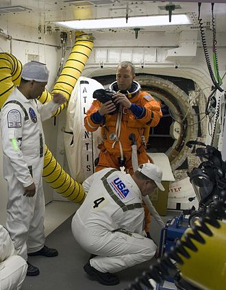 Service structure - Closeout crew members help astronaut Andrew Feustel in the  Launch Complex 39 white room prior to launch of STS-125