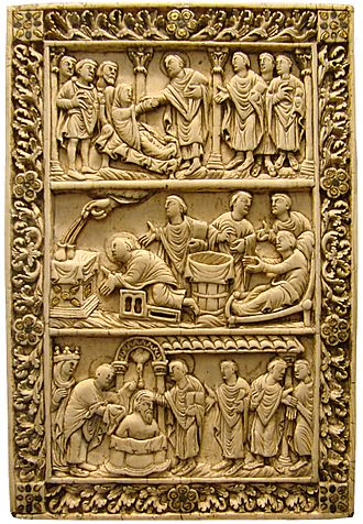 Saint Remigius - Late Carolingian ivory binding, c. 870, with miracles from the life of St Remi. Top: The dying pagan asks Saint Remi for baptism, Centre: the Hand of God fills the two vials, Bottom: the dove of the Holy spirit delivering the Sainte Ampoule at the Baptism of Clovis.  The plaque manages to cover two versions of the story.