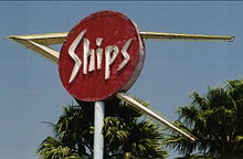 "Photograph of the top of a large sign on a pole. There is a red circular section with the word ""Ships"" written in neon tubing. There is a larger, sideways ""V"" shape whose arms pass through the sign and intersect a few feet to the left of the circle. The tops of two palm trees are visible just behind the sign."
