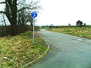 Narrow single carriageway, with wide grass verges, in a flat rural landscape