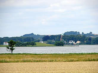 Skanderborg - Skanderborg Lake as seen from the northeast, with Kalvø and the remaining red brick castle church, once associated with Skanderborg Castle. The beech trees behind the church are the outskirts of Skanderborg Dyrehave.