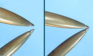 "First surface mirror - Example of a second surface mirror (left) and a first surface mirror (right). In both pictures, the pen is touching the surface of the mirror. ""Ghosting"" (a faint reflection from the first layer) is visible in the left image (more obvious in the full-size version)."