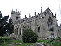 Una iglesia de piedra gris vista desde el sureste, que muestra un presbiterio con una ventana perpendicular al este, un parapeto calado y pináculos y, más allá de eso, la nave y una torre, también con pináculos