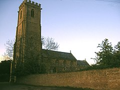 Stone building with square tower, partially obscured by trees