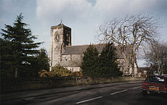 A church with a red tiled roof and a square tower. Trees in the foreground partially obscure the building. The sky is overcast and grey.