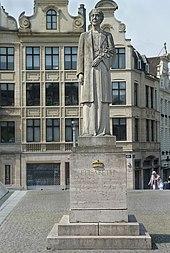 statue en pierre de Massangis (gris pâle) représentant la reine debout sur un socle au milieu d'une petite place