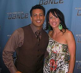 A strong Filipino man in a brown suit poses for a picture with his Italian wife who is wearing a colorful zebra print dress.