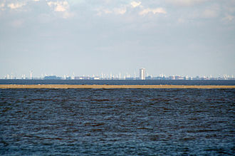Tertius (sandbank) - Tertius at low tide, with the city of Büsum in the background. Seals and seabirds can be seen dotting the exposed sandbank