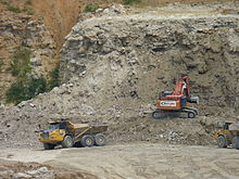 A photograph showing quarrying operations with a mechanical digger in the centre extracting rock from a cliff face. To the left, a lorry is just leaving with a full load of rock, and to the right, another lorry is waiting to collect its load from the digger.