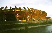 Exterior view of a stadium from across a river