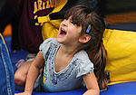 The daughter of U.S. Army Sgt. Edward Churde, with the Forward Support Company, 6th Engineer Battalion, 2nd Engineer Brigade, laughs as she climbs out of a bounce house during the brigade's special event 120810-F-LX370-461.jpg