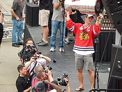 A man named Jonathan Toews, lifts the Stanley Cup.