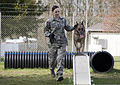 U.S. Air Force Staff Sgt. Shannon Hennessy, a military working dog handler with the 52nd Security Forces Squadron (SFS), runs through an obedience course with Katya, a military working dog with the 52nd SFS 140319-F-NJ596-090.jpg