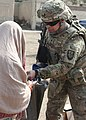 U.S. Army Maj. Ephraim Garcia gives a woman winter clothes at a camp for internally displaced persons in Kabul, Afghanistan, Oct. 7, 2011 111007-A-EM852-012.jpg