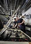 U.S. Navy Aviation Support Technicians (Equipment) 2nd Class John P. Ringer, front, and 3rd Class David Steffon perform an electrical system check on a dolly in the hangar bay aboard the aircraft carrier USS 130607-N-TX484-044.jpg