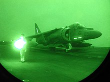 Mostly dark with green hue, this is a night-vision of jet aircraft getting ready for launch