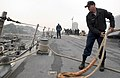 US Navy 060411-N-9851B-004 Boatswain's Mate 3rd Class Lucas Alderson pulls a mooring line onto the deck of Arleigh Burke-Class guided missile destroyer USS John S. McCain (DDG 56).jpg