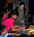 US Navy 071218-N-4774B-479 U.S. Marine Sgt. Marilyn Zeledon, network administrator for the 11th Marine Expeditionary Unit (MEU), shows some children from Singapore an exhibit on liquid nitrogen at the Singapore Science Museum.jpg